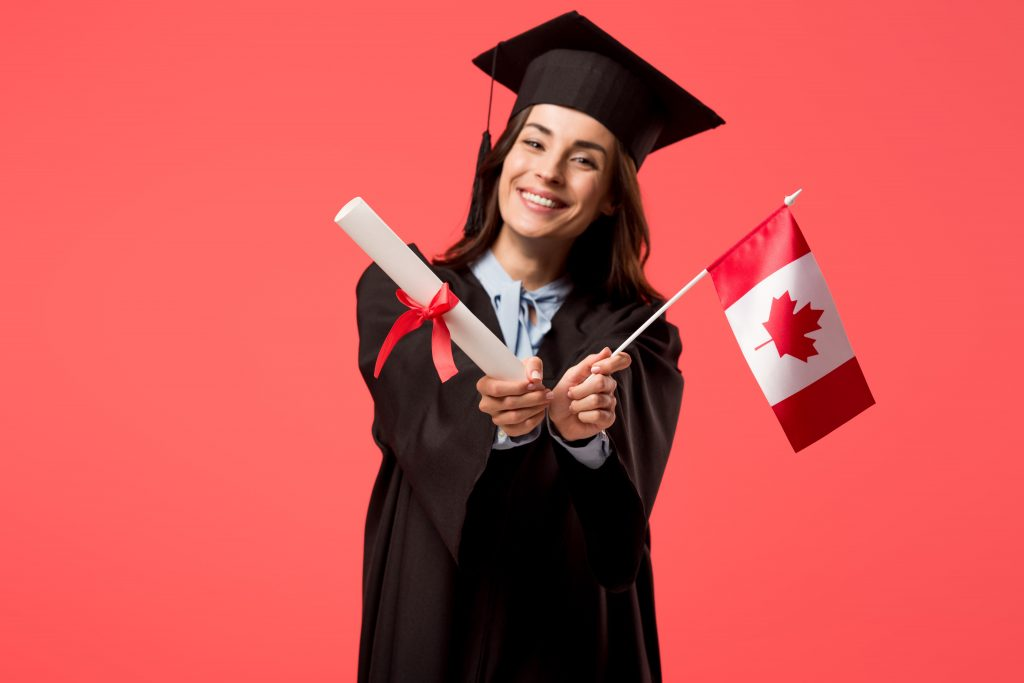 Graduate holding diploma and Canadian flag